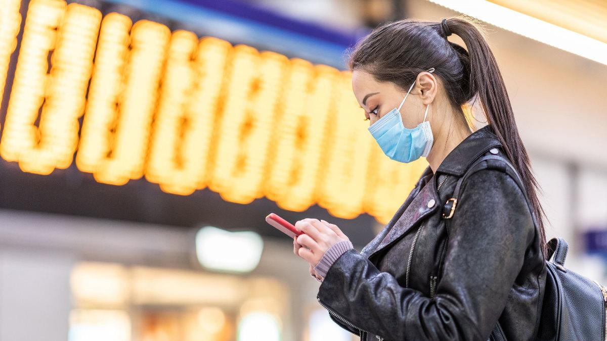 Joven asiática se protege del coronavirus con una mascarilla en un aeropuerto