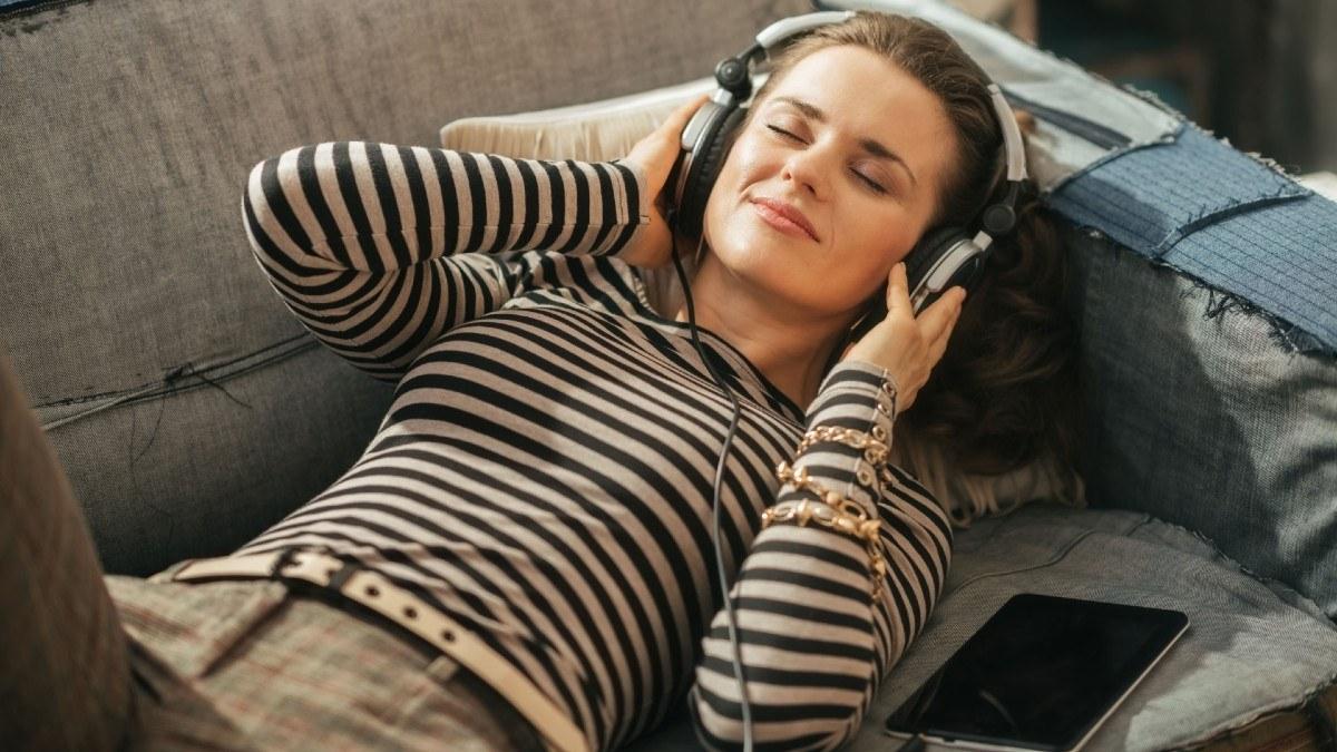 Mujer se relaja en el sofá mientras escucha audio digital en la nueva normalidad