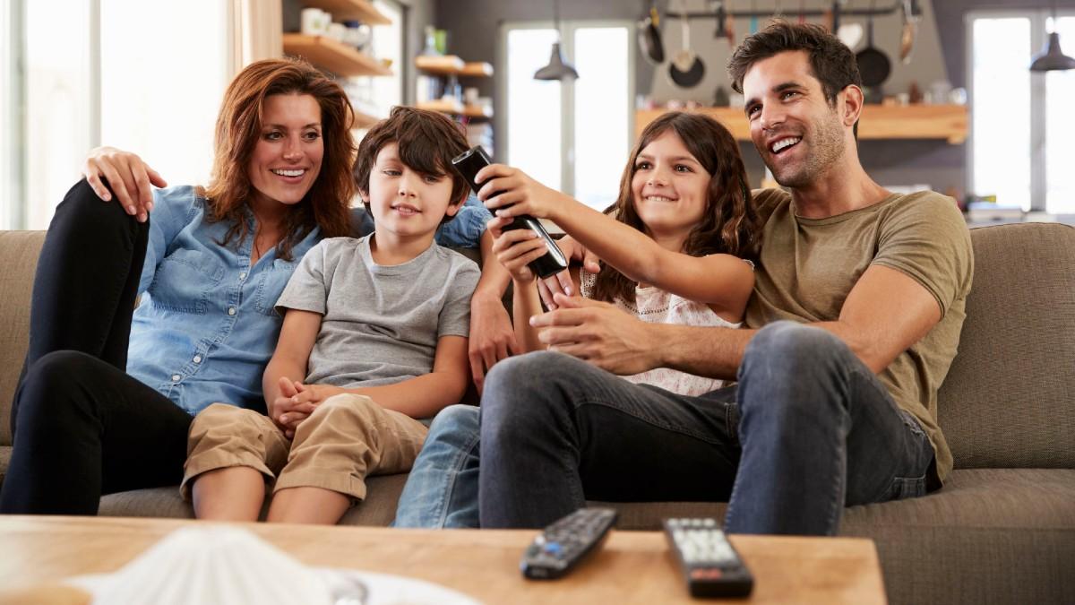 Consumo audiovisual digital poscovid: familia sentada en el sofá viendo la TV