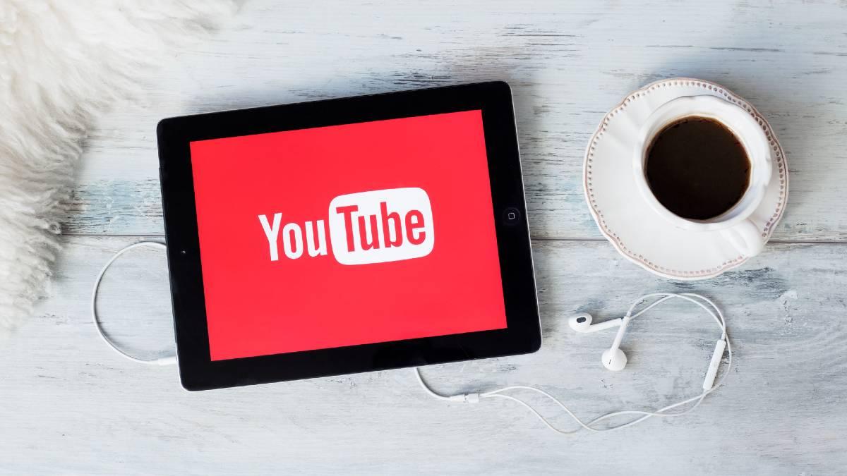 Sesión de YouTube abriéndose en una tablet, junto a un café