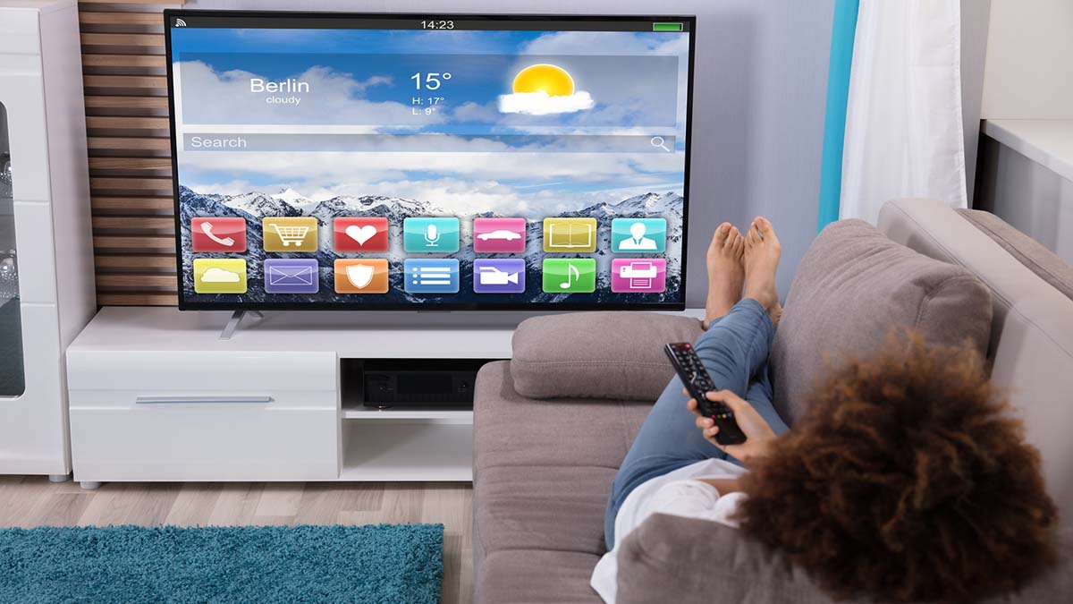 A woman watches content on her Connected TV from her sofa